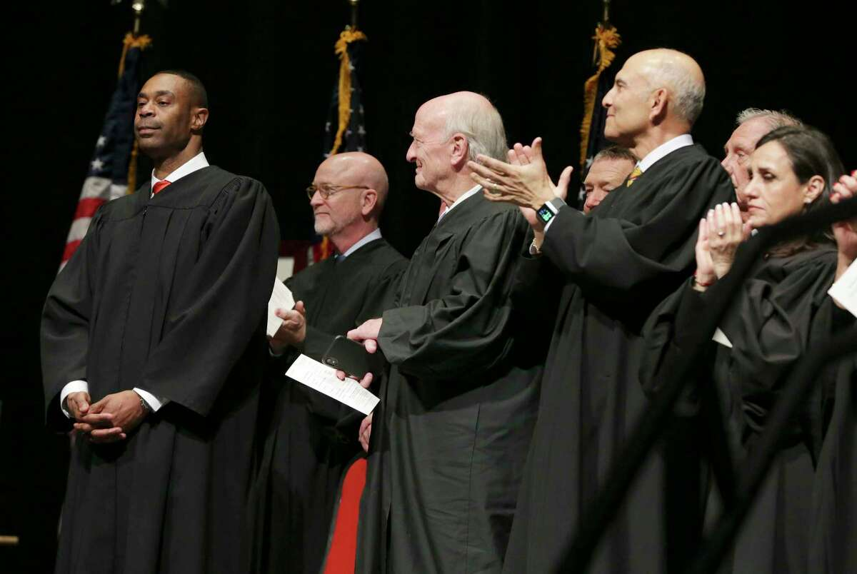 Jason K. Pulliam, the first African-American appointed as a federal judge in the U.S. District Court's Western District of Texas, formally takes the oath of office and stands among his peers during an investiture ceremony at the Lila Cockrell Theater on Thursday.