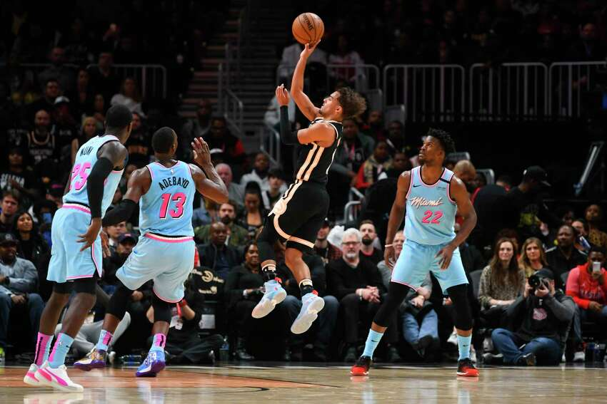 Atlanta Hawks guard Trae Young, second from right, shoots between Miami Heat forward Bam Adebayo (13) and forward Jimmy Butler (22) during the second half of an NBA basketball game Thursday, Feb. 20, 2020, in Atlanta. (AP Photo/John Amis)