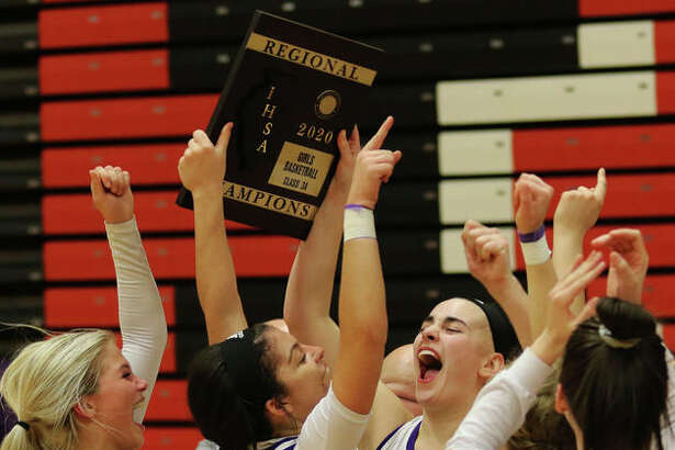 CM seniors Anna Hall (middle right) and Kourtland Tyus (middle left), sophomore Kelbie Zupan and teammates celebrate with the regional plaque Thursday night in Troy.