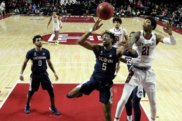 Temple's Justyn Hamilton, right, and UConn's Isaiah Whaley , center, battle for a rebound during the first half of an NCAA college basketball game in Philadelphia, Thursday, Feb. 20, 2020.