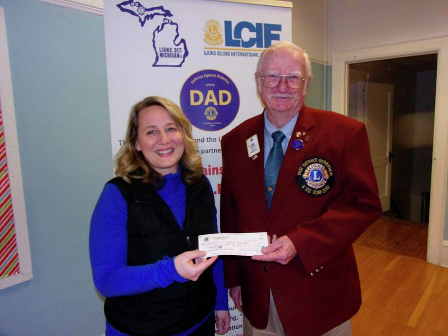 Corteva AgriScience Occupational Health Nurse Stacey Kadar presents a check to Immediate Past Lions Club District Governor Jack Kriete. (Rich Harp/For the Tribune)