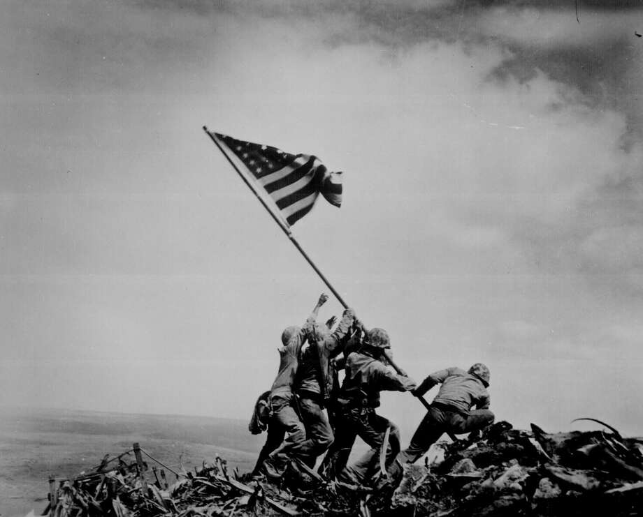 On Feb. 23, 1945, during the battle for Iwo Jima, U.S. Marines raised a flag atop Mount Suribachi. It was taken down, and a second flag was raised. Now part of U.S. Navy records, it is one of the most famous war photographs in U.S. history. Photo: Joe Rosenthal / U.S. Navy / U.S. Navy