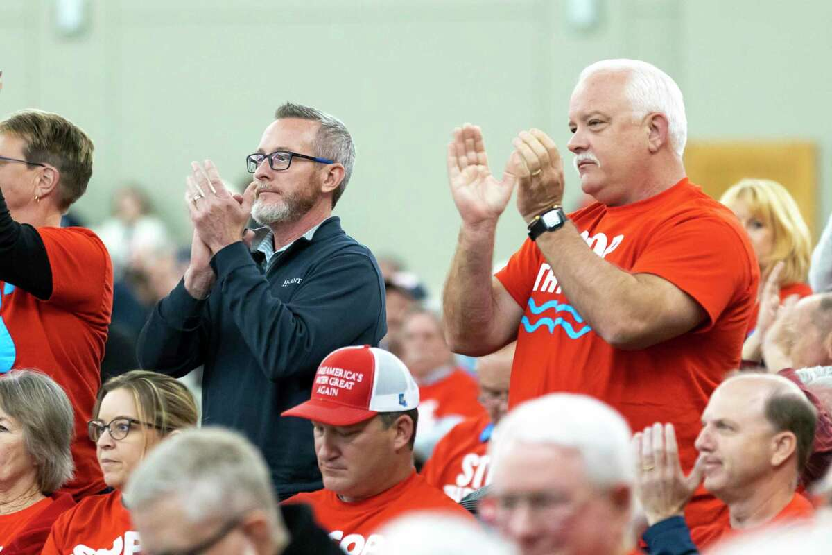 Montgomery County residents clap as State Representative Will Metcalf, R-Conroe, speaks on behalf of his constituents to continue the lowering of Lake Conroe at the Lone Star Convention Center in Conroe, Thursday, Feb. 20, 2020.