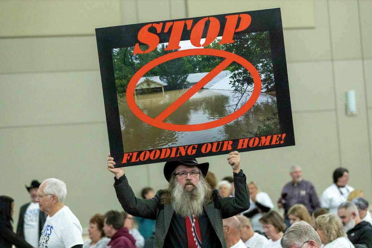 Frantisek Uncajtykholds an image of his flooded from Hurricane Harveyduring a San Jacinto River Authority meeting at the Lone Star Convention Center in Conroe, Thursday, Feb. 20, 2020.