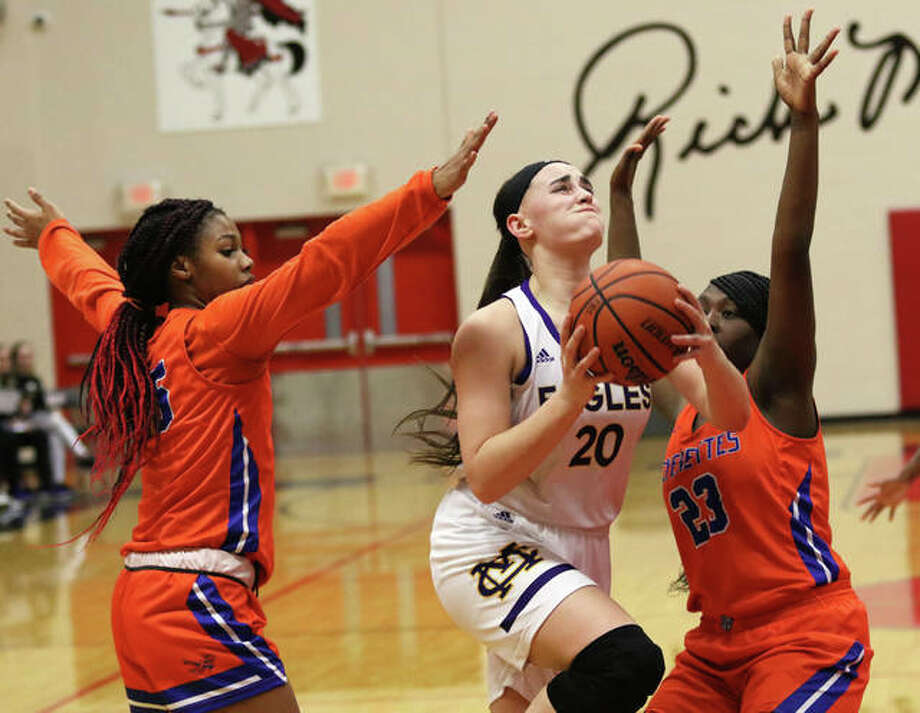CM's Anna Hall takes the ball to the basket between East St. Louis' Rickall Witcher (right) and Jazzman Westly-Young (left) in the first half Thursday night in the championship game of the Triad Class 3A Regional at Rich Mason Gym in Troy. Photo: Greg Shashack / The Telegraph