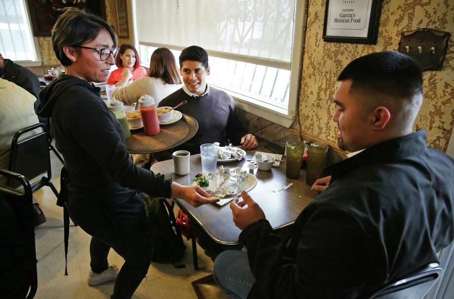 Saldaña, center, and fellow South San High graduate Jesus Rendow, right, meet for lunch at Garcia's on Fredericksburg Road. Photo: Bob Owen /San Antonio Express-News / San Antonio Express-News