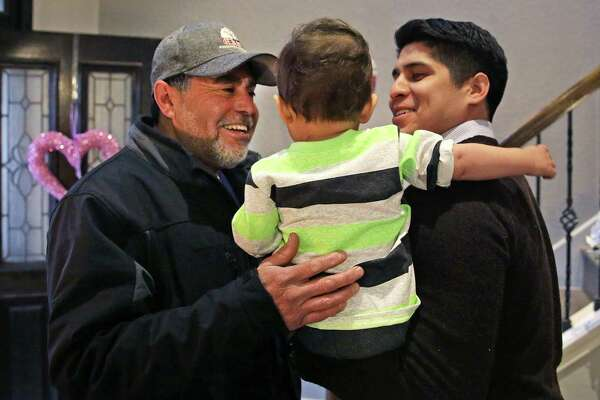 Saldaña, right, and his son Eli greet his father, Reynold Saldaña, as he arrives home from work.