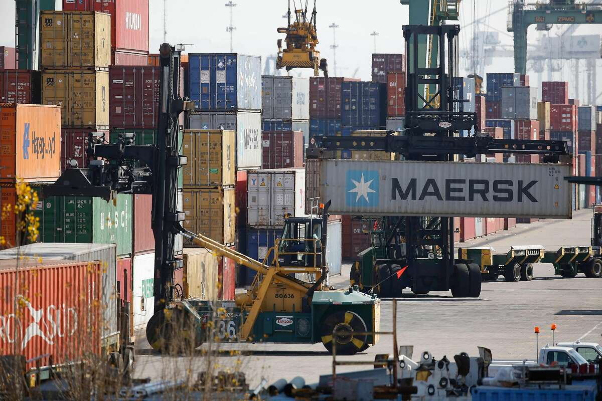 Containers are moved from trucks and stacked at the Port of Oakland on Thursday, February 20, 2020 in Oakland, Calif.