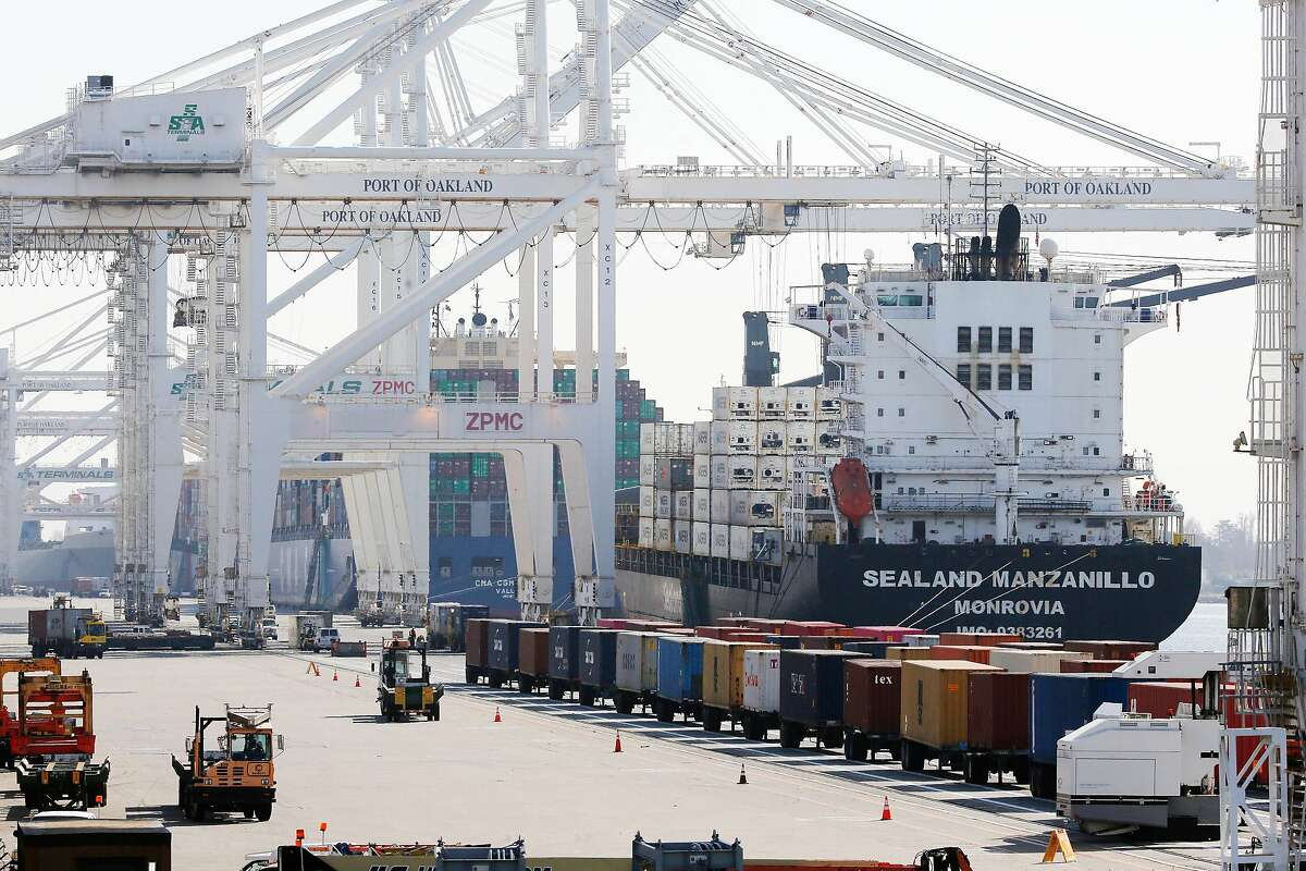 Vehicles drive past rows of containers on trailers seen next to a ship at the Port of Oakland on Thursday, February 20, 2020 in Oakland, Calif.