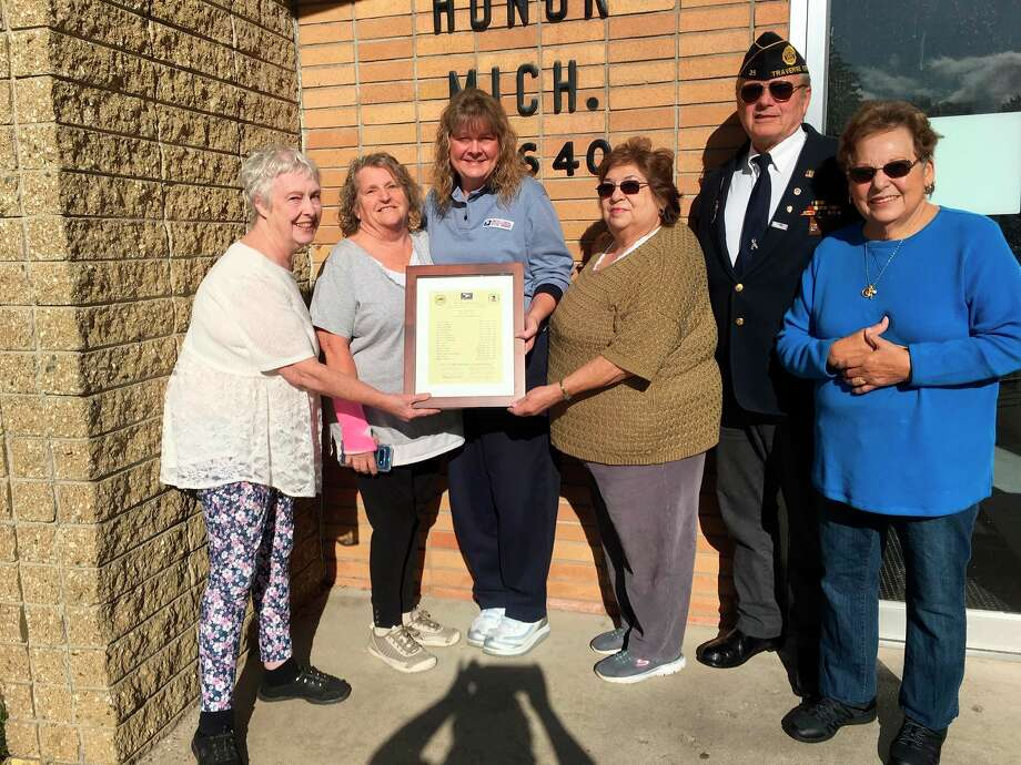 Pictured left to right : Sharon Osobrne, Patricia DeLorme, Rhonda Mullins, Carolyn Bailey, John Milks and Marie Cote, with the document containing every postmaster and postmistress serving Honor since 1895. (Courtesy Photo/Honor Historical Society)