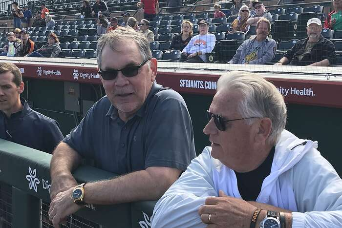 Former manager Bruce Bochy chats with broadcaster Duane Kuiper as they watch Friday's workout at Scottsdale Stadium.