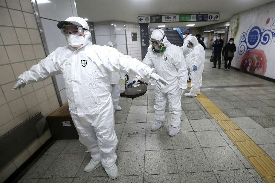 """Emergency workers help clean each other's protective suits after disinfecting a subway station in Seoul. """"We have entered an emergency phase, """" said Prime Minister Chung Se-kyun. Photo: Ahn Young-joon / Associated Press"""