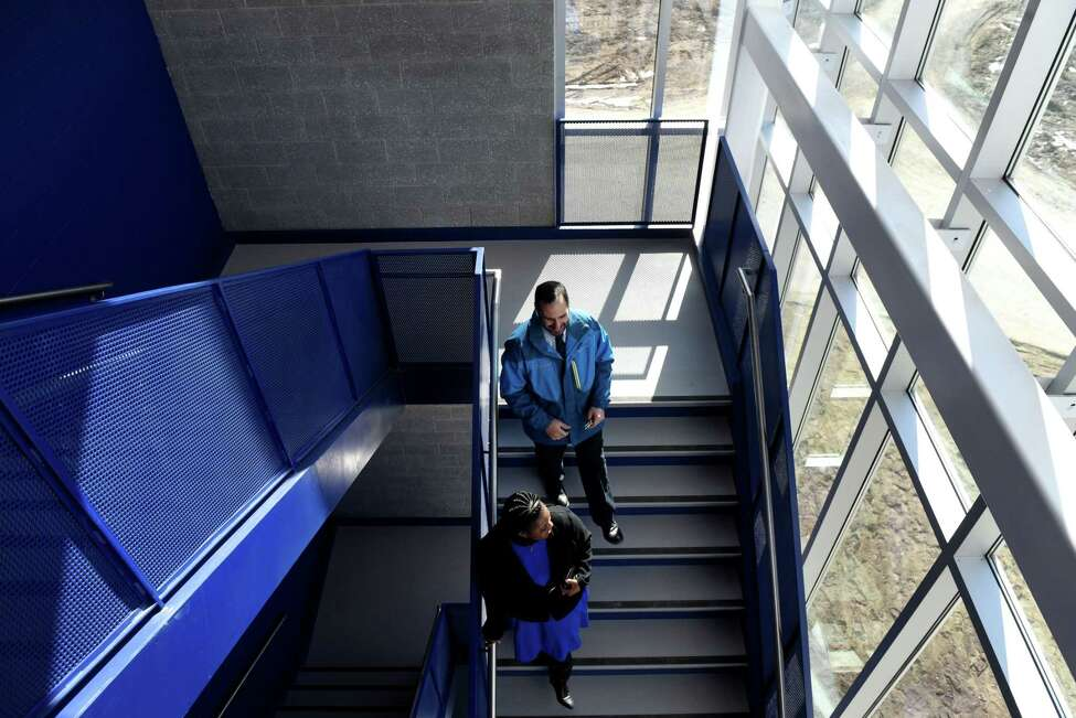 Scott DePhillips, the project manager from Turner Construction, top, and Albany School District Superintendent Kaweeda Adams head down a stairwell inside the new Albany High School expansion on Friday, Feb. 21, 2020, in Albany, N.Y. The improvements are part of the first phase of the district?•s $180 million renovation and expansion of the school. (Will Waldron/Times Union)