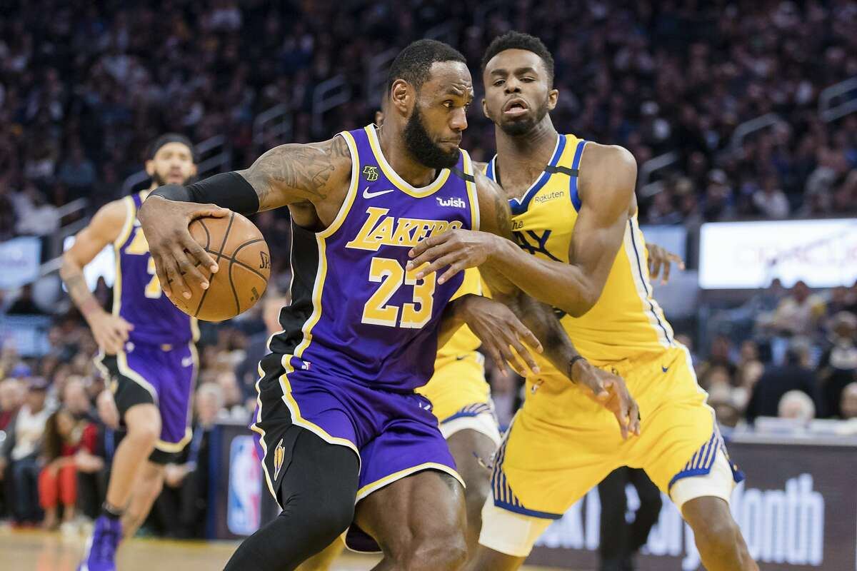 Los Angeles Lakers forward LeBron James (23) drives to the basket as Golden State Warriors guard Andrew Wiggins defends in the first half of an NBA basketball game in San Francisco Saturday, Feb. 8, 2020. (AP Photo/John Hefti)