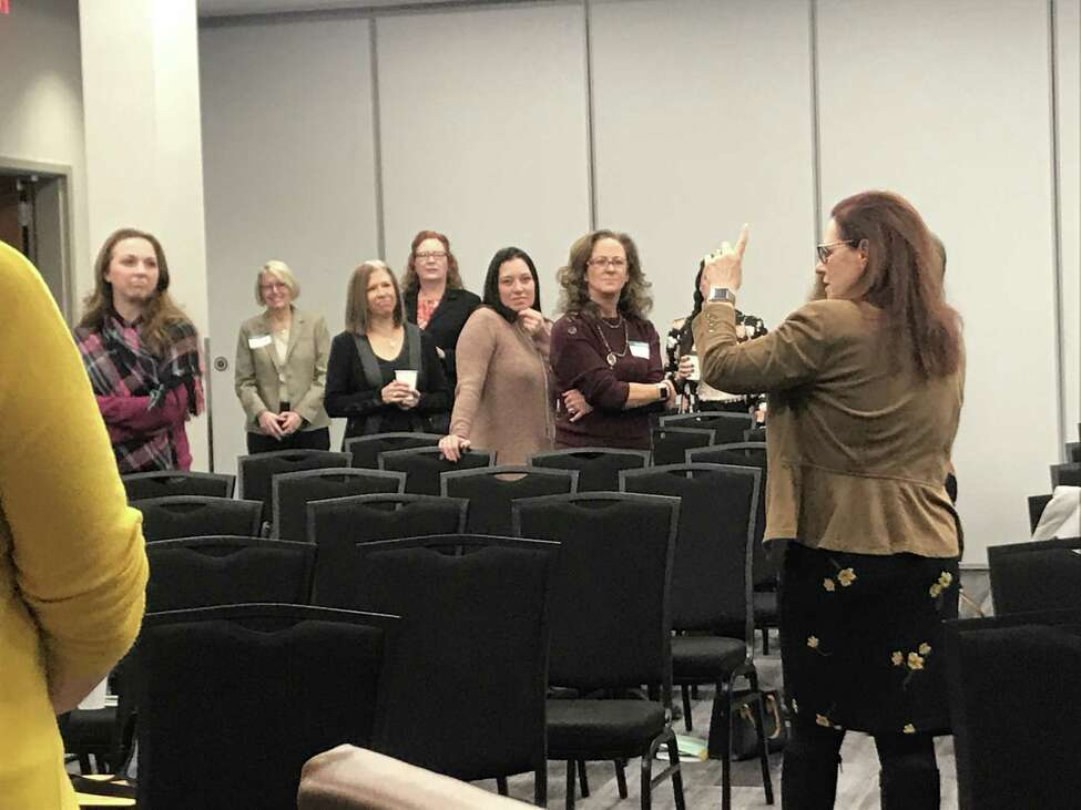 Kat Koppett has everyone get out of their chairs and group up for an improv-based exercise during her November breakfast event. (Photo by Sara Tracey)