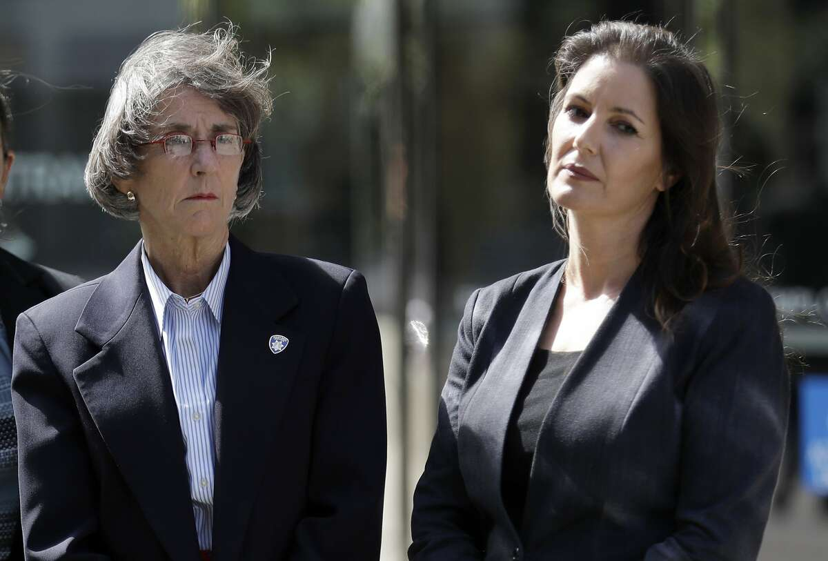 FILE - In this July 10, 2017 file photo, Oakland, Calif., Police Chief Anne Kirkpatrick, left, and Mayor Libby Schaaf wait to talk to the media after a federal court hearing in San Francisco. The Oakland Police Commission voted unanimously Thursday, Feb. 202, 2020, to fire the city's first female police chief without cause. Commission chair, Regina Jackson, says Kirkpatrick's ouster comes after the department failed to comply with court-ordered reforms. The decision was supported by Oakland Mayor Libby Schaaf, who appointed Kirkpatrick in 2017.