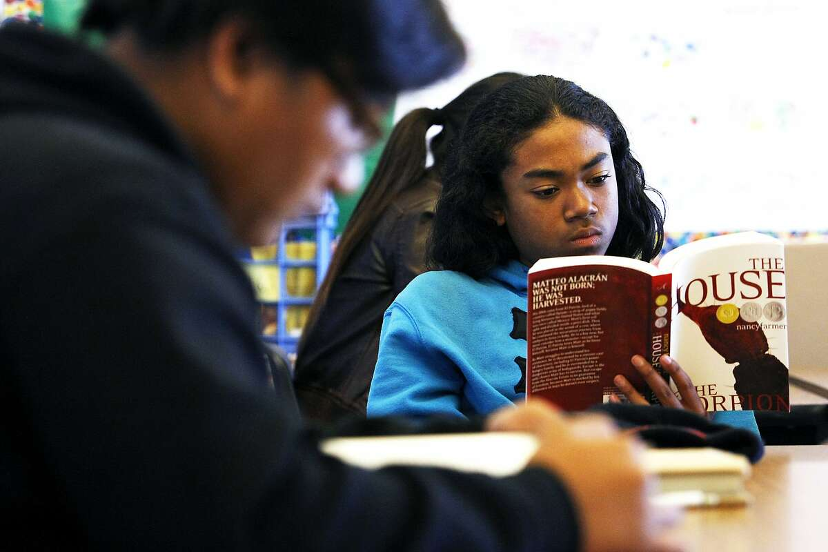 Student Owen Lagumbay, right, is seen reading a book of his choice during an 8th grade language arts class at James Denman Middle School in San Francisco, CA Thursday, November 7, 2013.