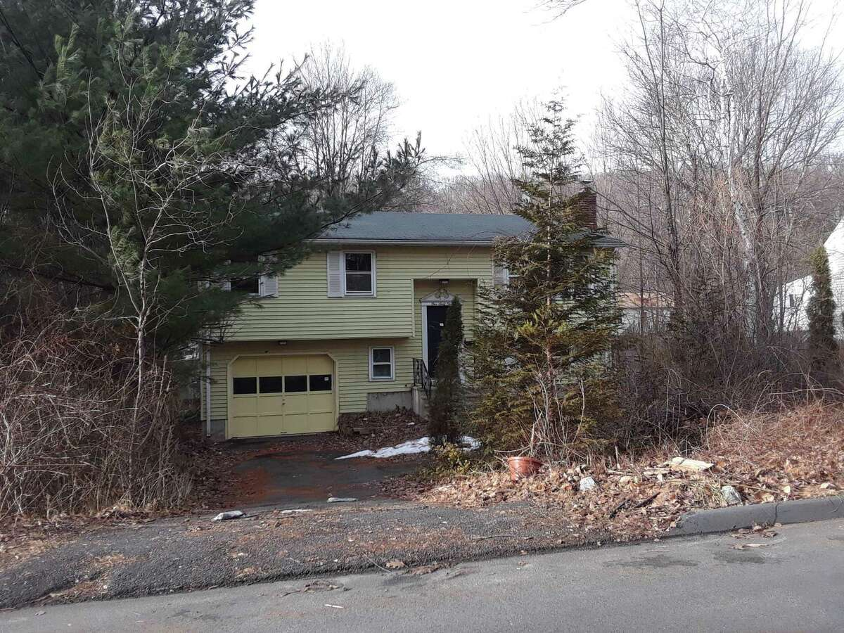 Above, an unoccupied house in Torrington has a number of blight violations.
