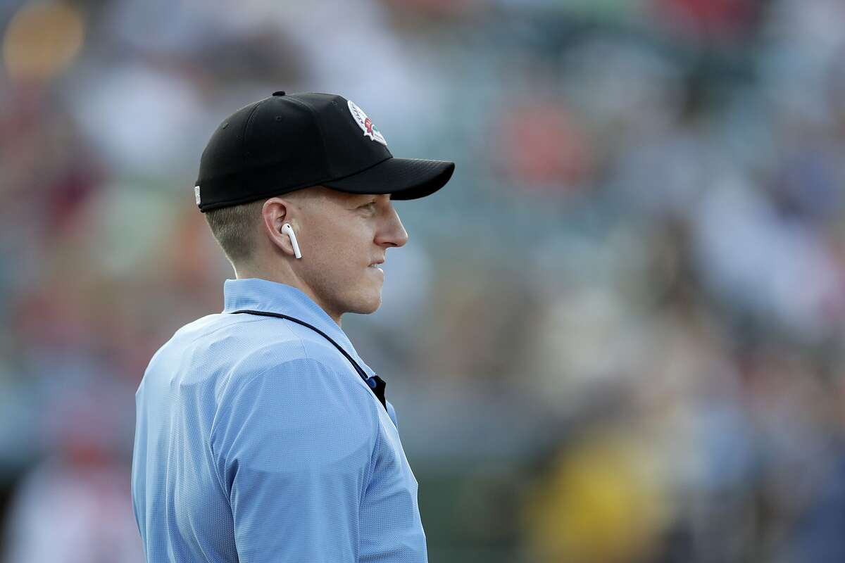 Home plate umpire Brian deBrauwere looks on while wearing an earpiece connected to a ball and strikes calling system prior to the start of the Atlantic League All-Star minor league baseball game, Wednesday, July 10, 2019, in York, Pa. deBrauwere wore the earpiece connected to an iPhone in his ball bag which relayed ball and strike calls upon receiving it from a TrackMan computer system that uses Doppler radar. The independent Atlantic League became the first American professional baseball league to let the computer call balls and strikes during the all star game.