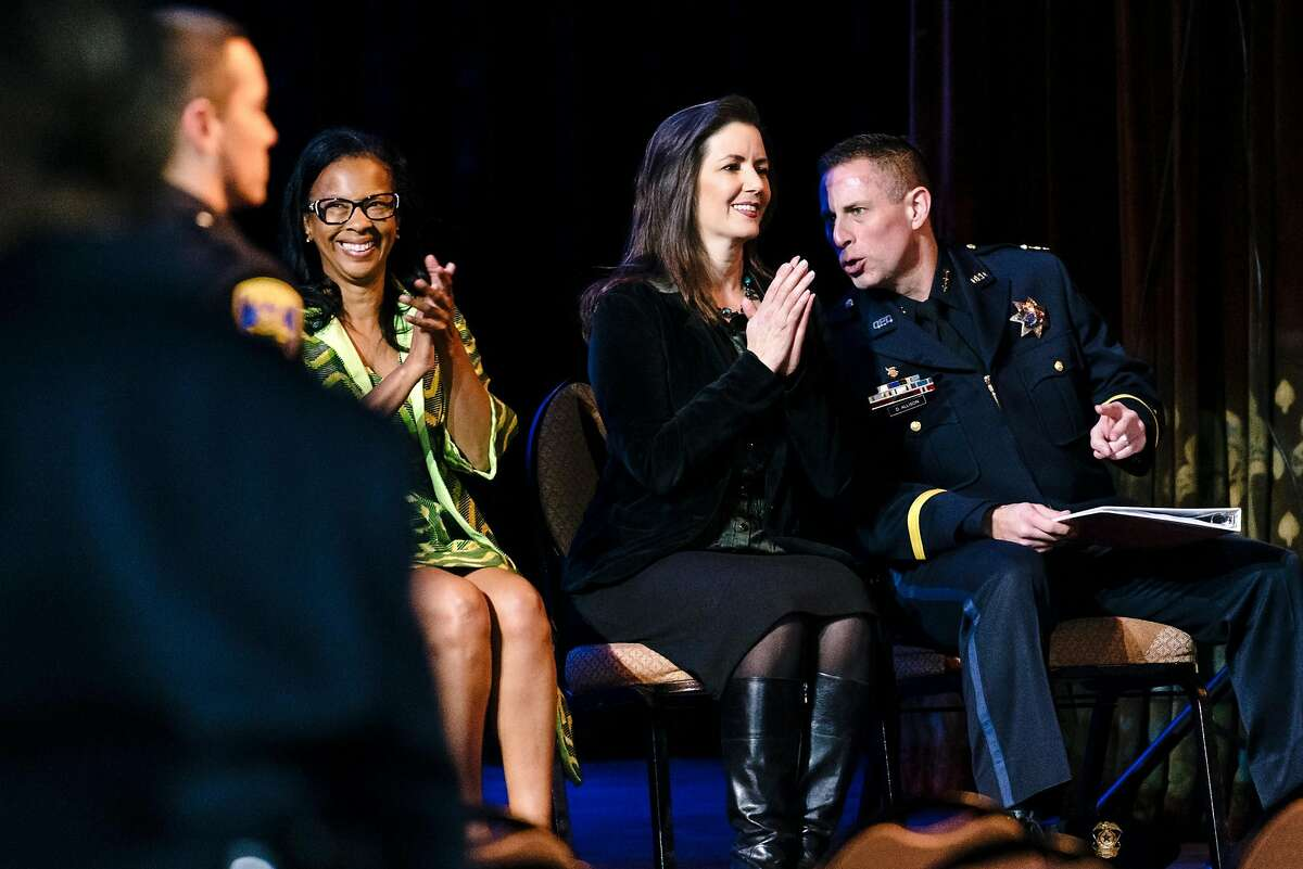 Acting Oakland Police Chief Darren Allison, right, leans in to say something to Oakland Mayor Libby Schaaf, as Oakland Police Commission chair Regina Jackson claps during the Oakland Police Department's 183rd Basic Recruit Academy Graduation held at the Scottish Rite Center in Oakland, California, on Friday, Feb. 21, 2020. The Oakland Police Commission voted unanimously in a closed session on Thursday to fire Police Chief Anne Kirkpatrick.