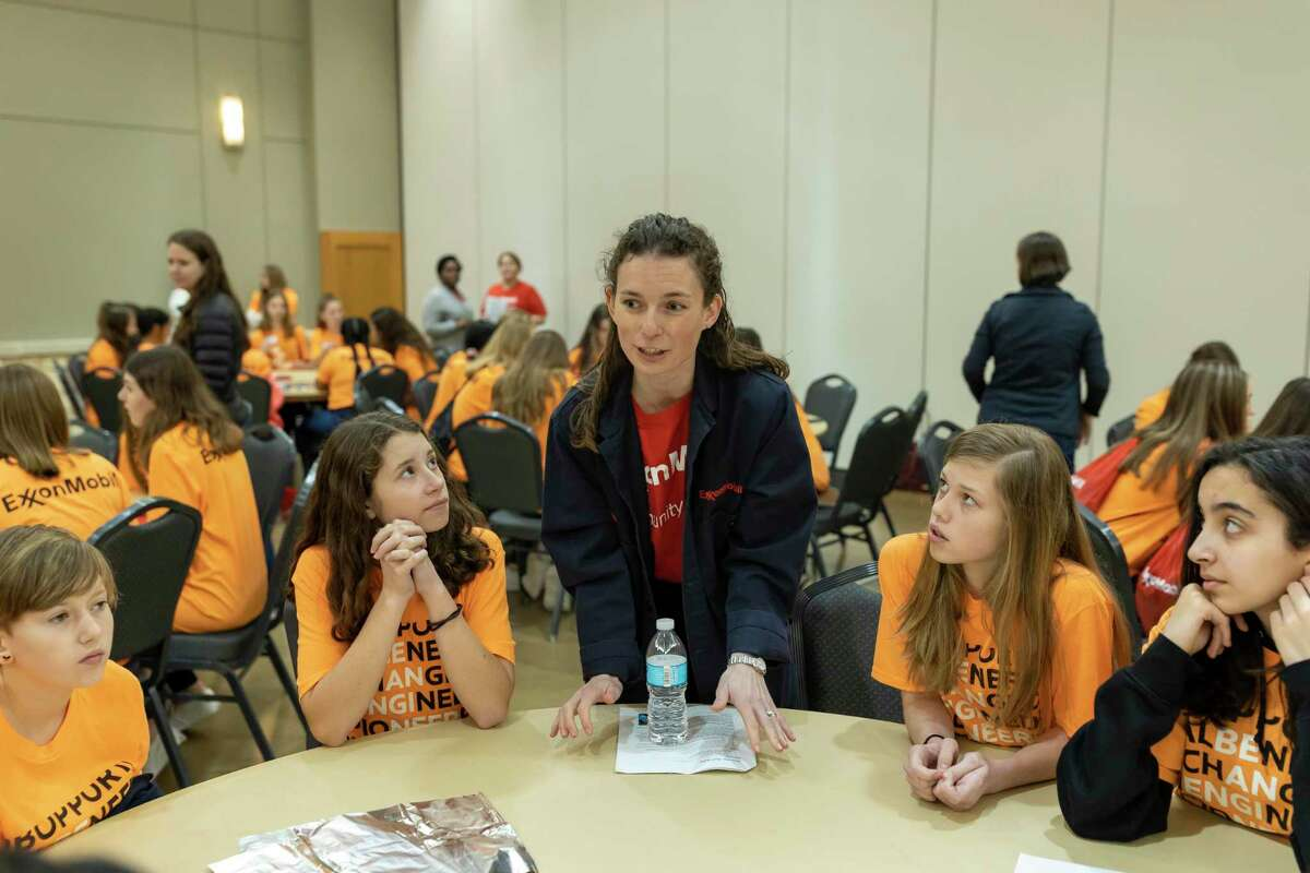An event volunteer instructs students from the CISD district during a hands-on workshop sponsored by ExxonMobil at Lone Star Convention Center in Conroe, Thursday, Feb. 20, 2020. The event titled Girl's Engineering Festival brought women engineers to speak with middle school students about working in S.T.E.M.