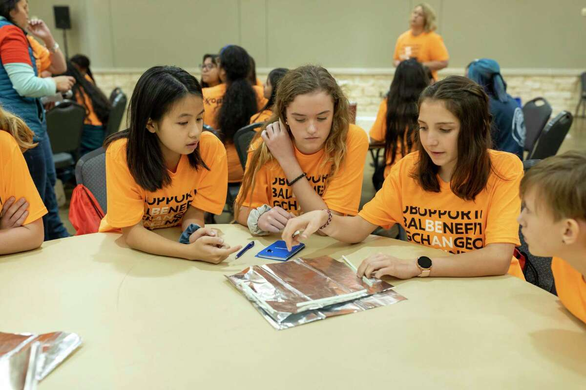 Acacia Siyu Zang, Calli Marie Hill and Sofia Valdes listen to an event volunteer during a hands-on workshop sponsored by ExxonMobil at Lone Star Convention Center in Conroe, Thursday, Feb. 20, 2020. The event titled Girl's Engineering Festival brought women engineers to speak with middle school students about working in S.T.E.M.