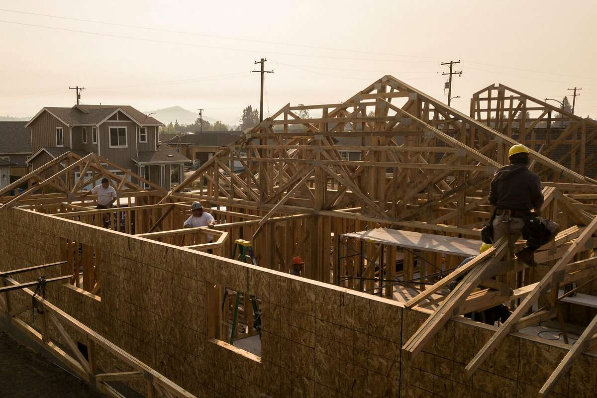 Prestige Home and Remodel Inc. workers build a home in the Coffey Park neighborhood as the Kincade Fire smoke fills the air on Friday, Oct. 25, 2019, in Santa Rosa, Calif. The Coffey Park neighborhood continues to rebuild after it was destroyed in the Tubbs Fire of October 2017.