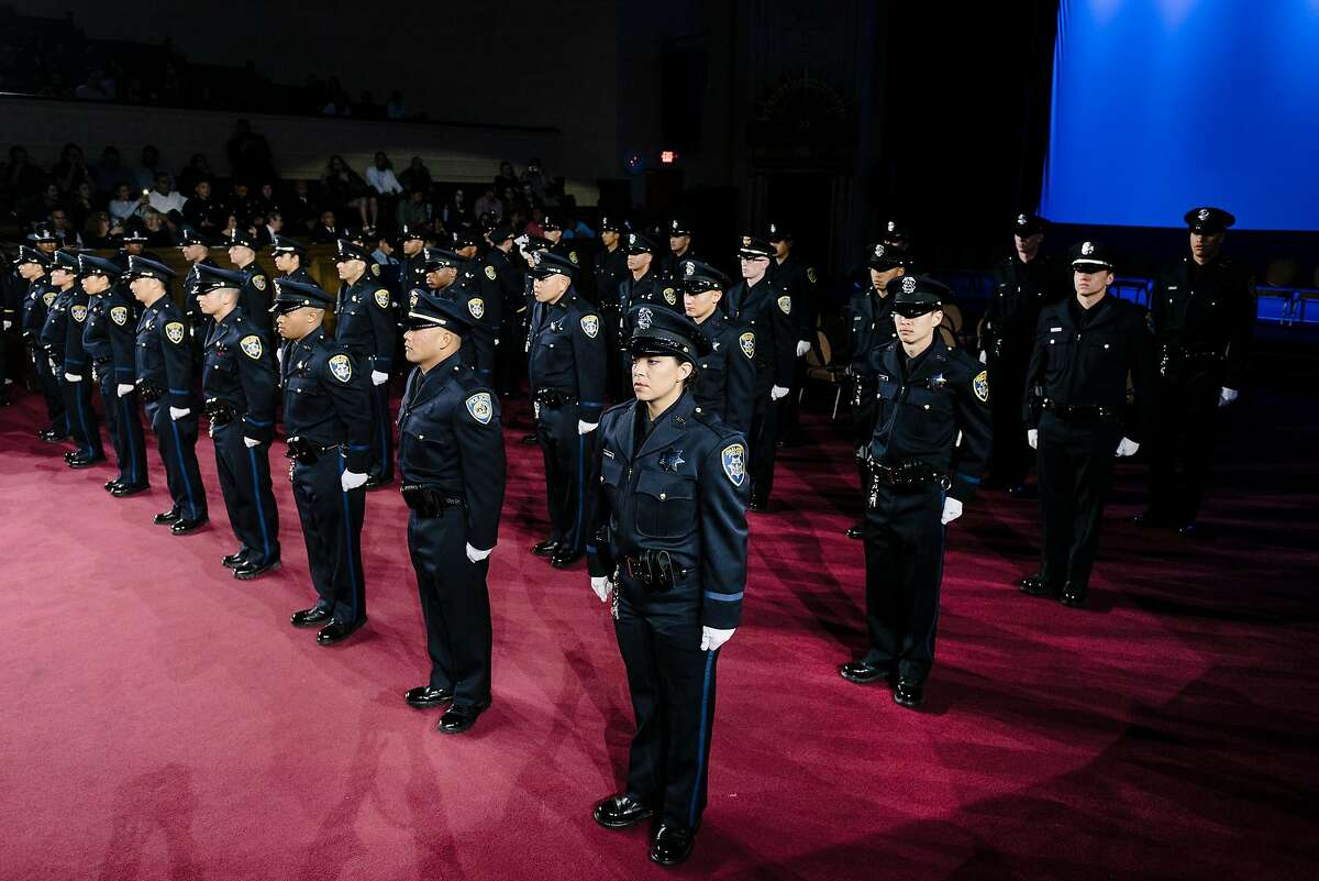 Graduating cadets stand at attention during the Oakland Police Department's 183rd Basic Recruit Academy Graduation at the Scottish Rite Center in Oakland in February. A proposed California law would require candidates to have at least a bachelor's degree, or wait until they are 25 years old, to enter a police academy.