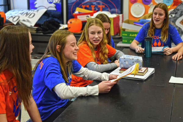 Eighth grade GO members engage and laugh during an impromptu meeting during their lunch period on Friday to go over their next week's agenda for Be-You-Nique Week at Lincoln Middle School.