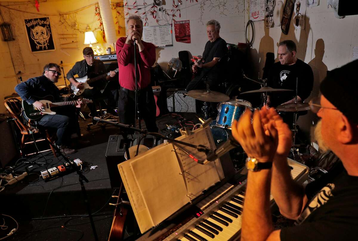"""Musicians, from left, Tom Heyman, Maurice Tani, Jello Biafra, Larry Levy, John Moreman, and Joshua Raoul Brody rehearing for """"Tribute for Ron Loney,"""" in San Francisco, Calif., on Thursday, February 20, 2020. Musicians fear that AB5, California's new gig-work law, will demolish their industry. We are photographing (who should be in the photo as well). We want a feeling of musicians rehearsing."""
