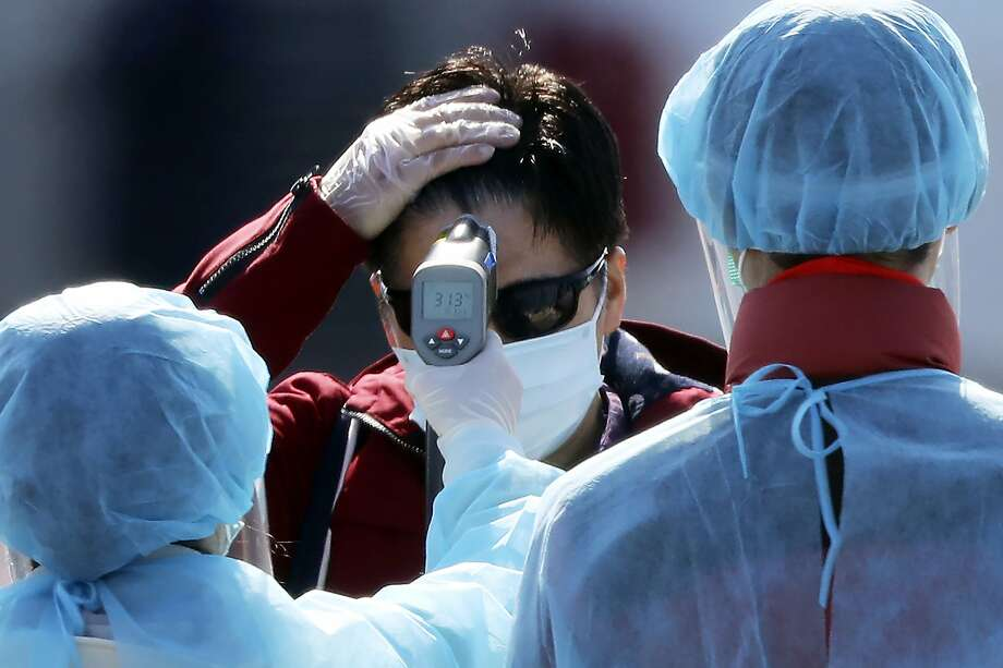 An official in protective suits measure the temperature of the foreign passengers disembarked from the quarantined Diamond Princess cruise ship before boarding to buses at a port in Yokohama, near Tokyo, Friday, Feb. 21, 2020. Japanese Prime Minister Shinzo Abe should be basking in the limelight this year in the runup to the 2020 Tokyo Olympics. Instead, the economy is reeling and criticism is mounting over his government's handling of a new virus that began in China and has spread alarmingly in Japan. (AP Photo/Eugene Hoshiko) Photo: Eugene Hoshiko, Associated Press