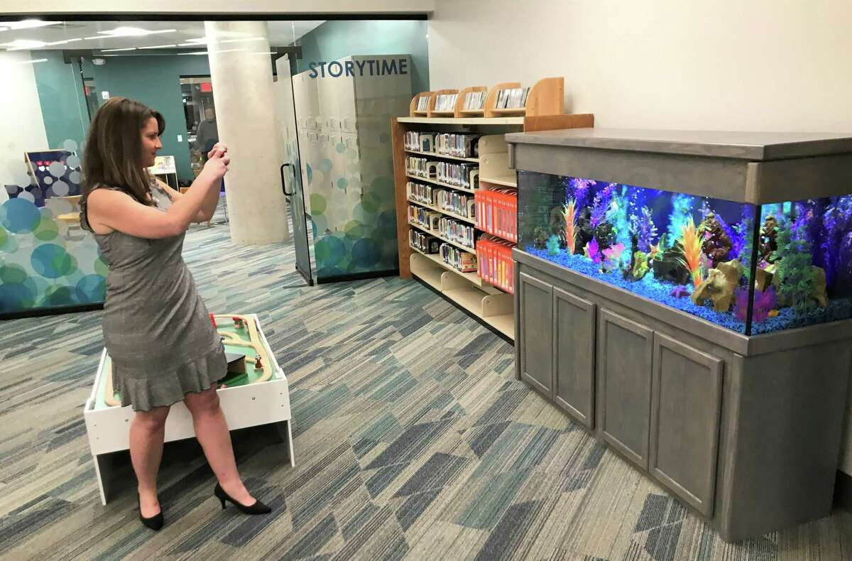 State Rep. Christie Carpino takes a photo of a new fish tank that has been installed in the Children's Library in Cromwell and is already a source of fascination for young patrons.