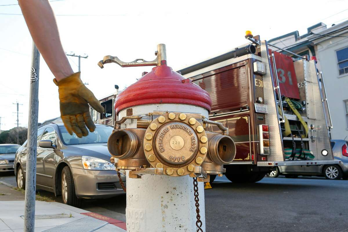 Firefighters demonstrate how a Greeson Valve is attached to one of high-pressure system hydrants on 12th Ave and Anza St. near Fire Station 31 on Wednesday, February 7, 2017 in San Francisco, California.
