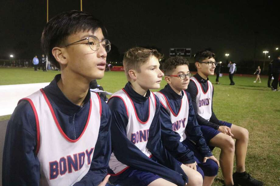 Waiting in the chilly night air for the 1600-meter runs to take place is the Bondy Intermediate foursome of (L-R) Vincent Mac, Jason Cruz, Charles Denham and Devin Lara. All are eighth graders except for Denham. Lara won the eighth-grade race in 5:36.66. Photo: Robert Avery