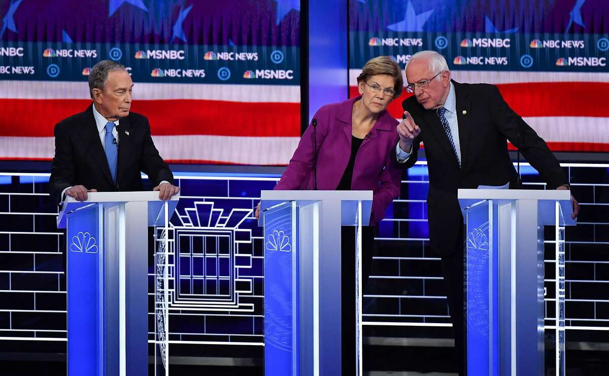 FILE - Democratic presidential hopefuls Former New York Mayor Mike Bloomberg (L) watches Massachusetts Senator Elizabeth Warren and Vermont Senator Bernie Sanders (R) talk during the ninth Democratic primary debate of the 2020 presidential campaign season co-hosted by NBC News, MSNBC, Noticias Telemundo and The Nevada Independent at the Paris Theater in Las Vegas, Nevada, on February 19, 2020.