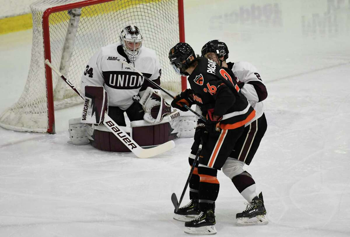 Union goaltender Darion Hanson (34) gloves a shot by Princeton forward Jake Paganelli (26) during the first period an NCAA hockey game in Schenectady, N.Y.,