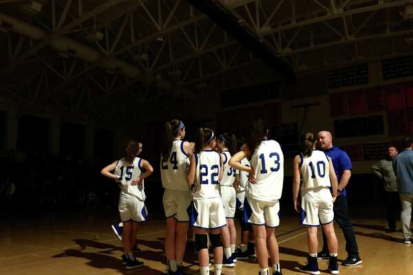 The Newtown girls backetball team huddles up after the lights went out at halftime of their SWC quarterfinal against rival New Milford on Friday, Feb. 21, 2020 at Newtown High School in Newtown, Conn.