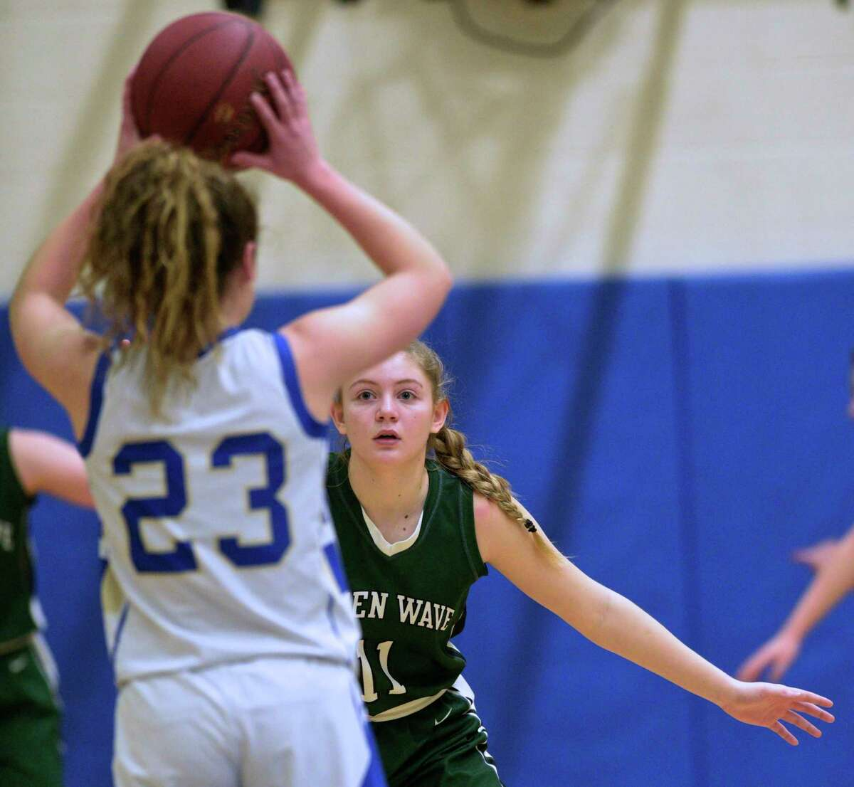 New Milford's Sydney Scalzo (11) keeps her eyes glued to Newtown's Shea Murphy (23) on Friday.