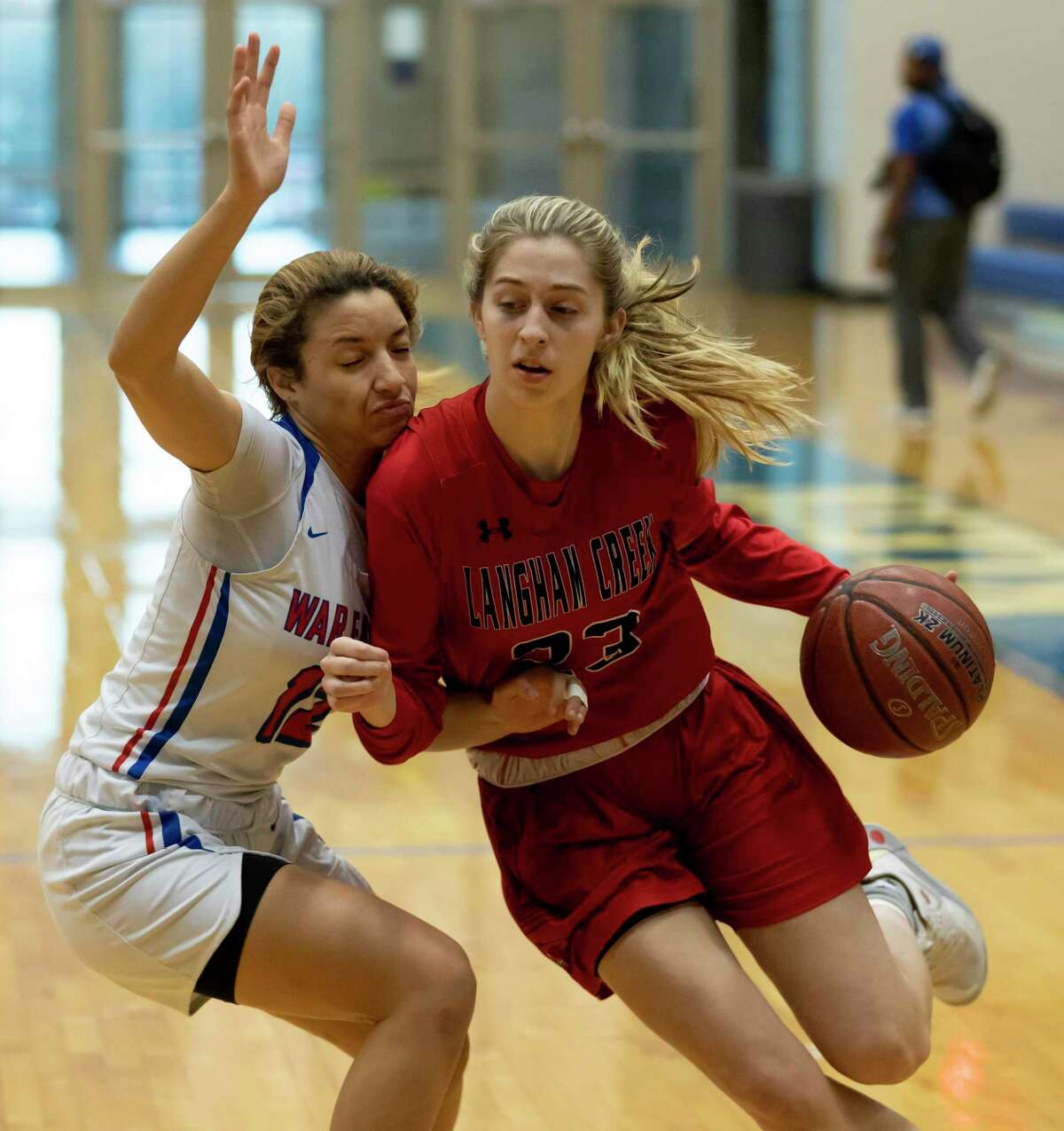 Langham Creek guard Kaley Perkins (23) dribbles the ball down the court while under pressure from Oak Ridge guard Mersadez Nephew (12) in a Region II-6A area girls basketball playoff during the first half at Klein high school, Tuesday, Feb. 21, 2020.