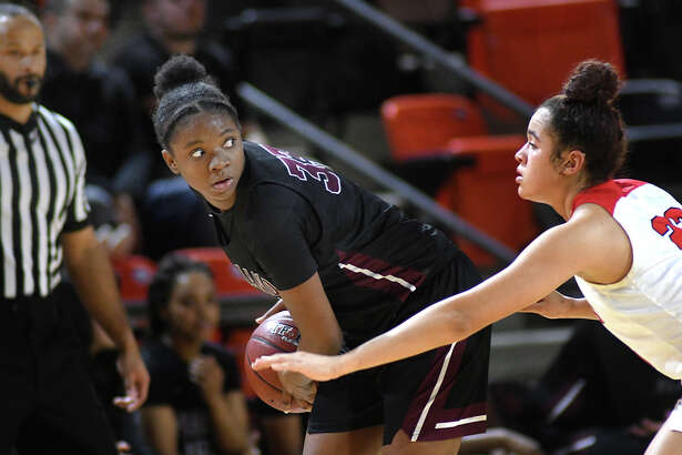 Pearland senior center De Gaston works the ball against Atascocita senior post Kyleigh McGuire during the 4th quarter of their UIL Girls' Basketball Region III Conference 6A Area Playoff matchup at LaPorte High School on Feb. 21, 2020.