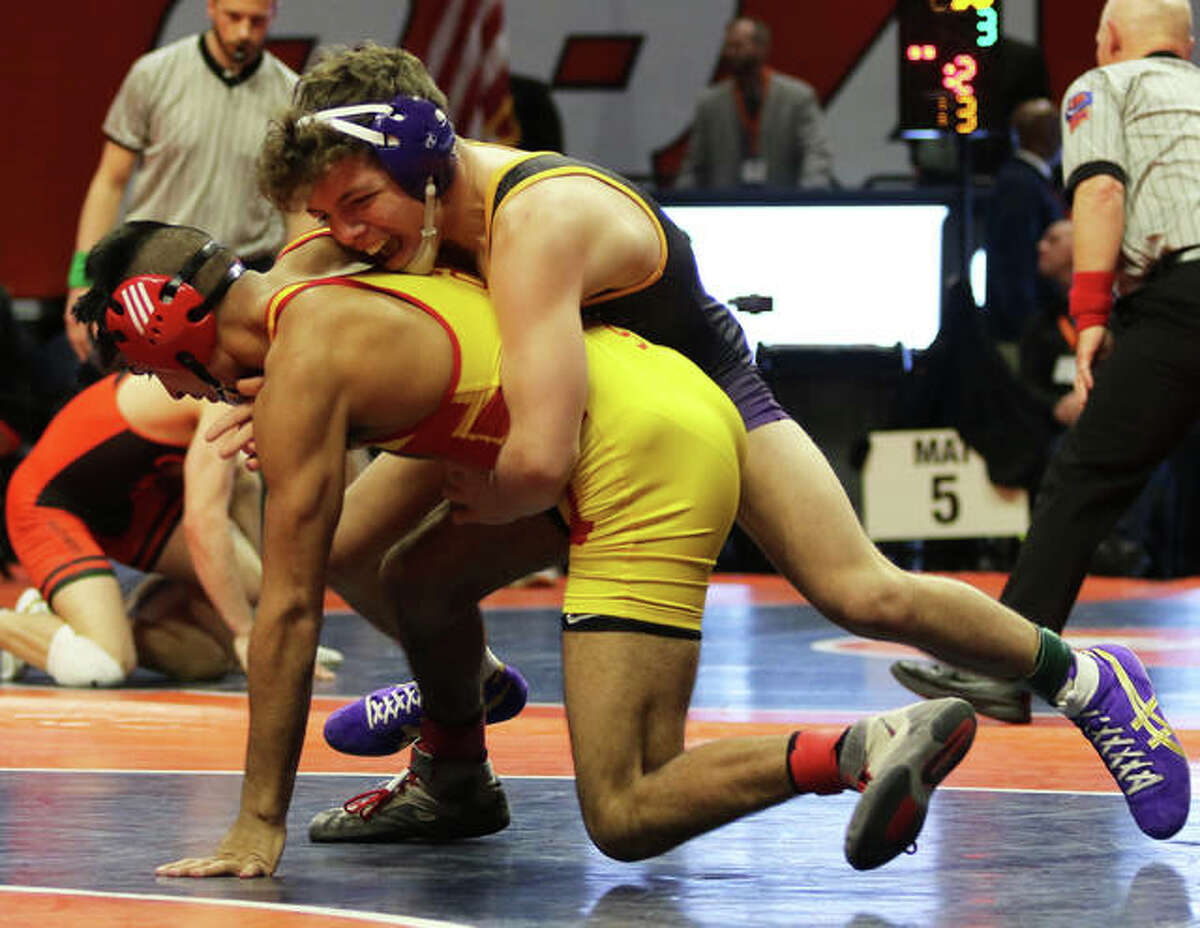 CM's Caleb Tyus (top) takes down Rock Island's Victor Guzman early in the first period of their 132-pound semifinal match at the Class 2A state tournament Friday night at State Farm Center in Champaign.