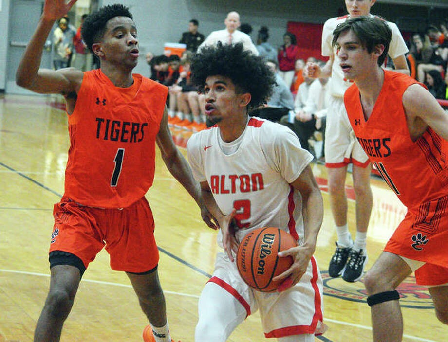 Alton's Andrew Jones, middle, drives to the basket during Friday's Southwestern Conference game against Edwardsville. Photo: Scott Marion | For The Telegraph