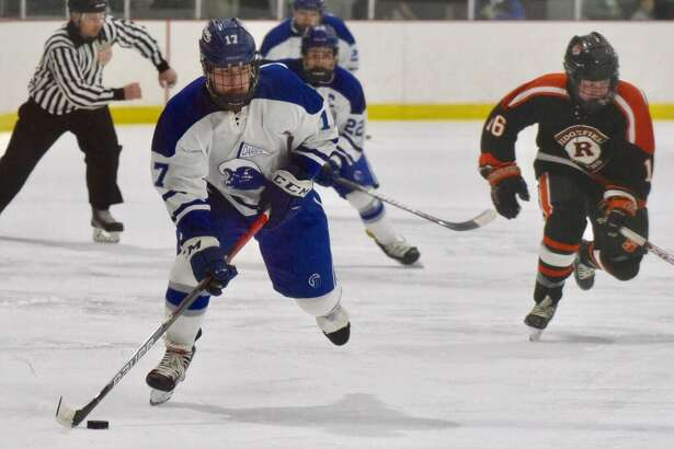 Darien's Jamison Moore (17) breaks out with the puck during a boys ice hockey game against Ridgefield at the Darien Ice House on Friday in Darien.