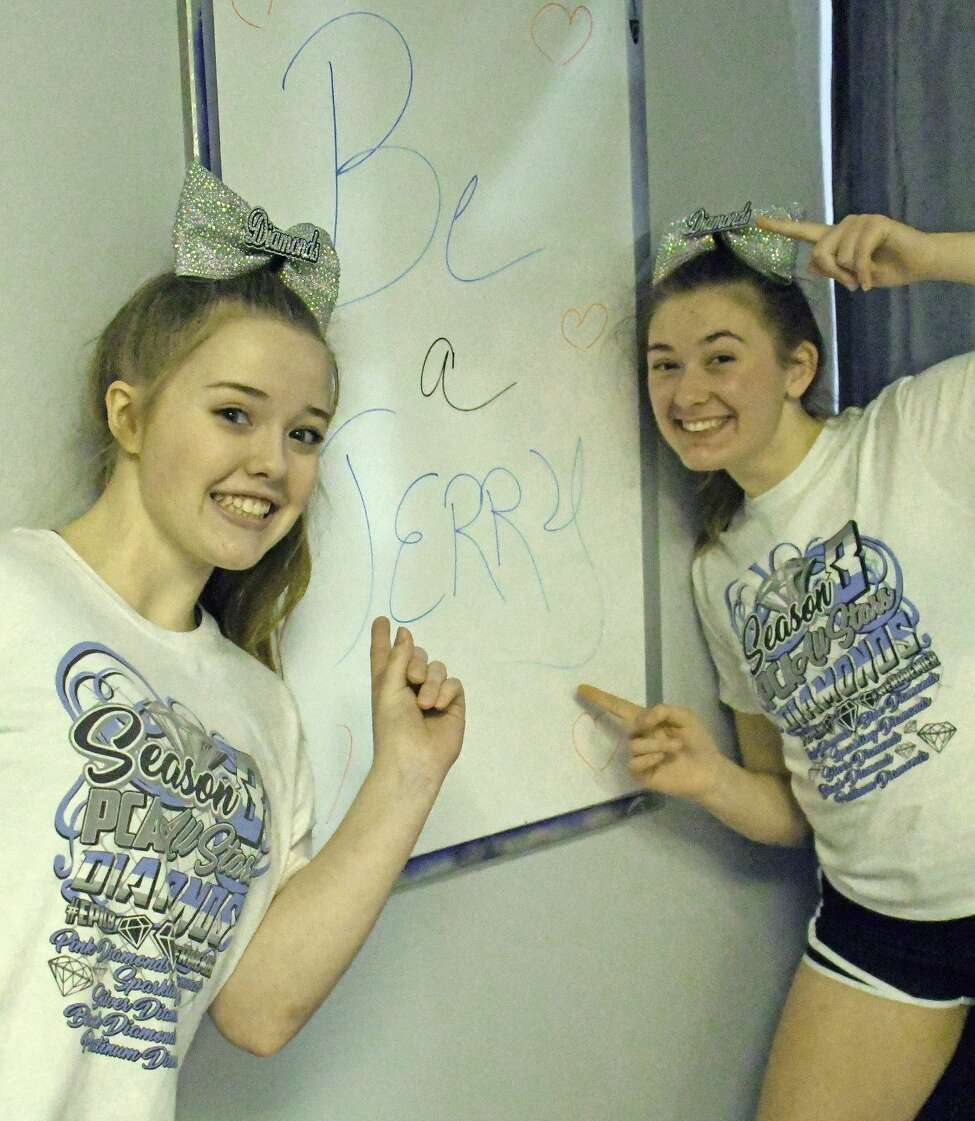 Members of the Premier Cheer Athletics, Madeline Green, left, and Alex Joslyn, point to a white board with the message