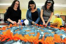 """Sabrina Sallati, of Bridgeport, left, Margie Otero, center, and her daughter Alyssa Rivera work together on a fleece blanket for the Monroe/Trumbull Chapter of the national non-profit organization Binky Patrol at Christ the King Church in Trumbull on Friday. The Binky Patrol works to make fleece tie blankets for childhood cancer fighters and other critically ill kids. Families will receive the blankets at the Bridgeport Sound Tigers """"Stick it 2 Cancer"""" Event on March 15."""