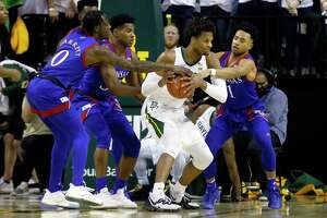 Kansas guard Marcus Garrett, left, and guard Devon Dotson, right, pressure Baylor forward Freddie Gillespie, center, during the first half of an NCAA college basketball game on Saturday, Feb. 22, 2020, in Waco, Texas. (AP Photo/Ray Carlin)