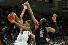 UConn's Crystal Dangerfield passes under the basket against Central Florida's Masseny Kaba (5) during the first half of Saturday's game in Storrs.