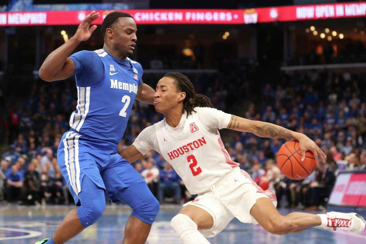 Houston guard Caleb Mills (2) drives the ball past Memphis guard Alex Lomax (2) in the first half of an NCAA college basketball game Saturday, Feb. 22, 2020, in Memphis, Tenn. (AP Photo/Karen Pulfer Focht)