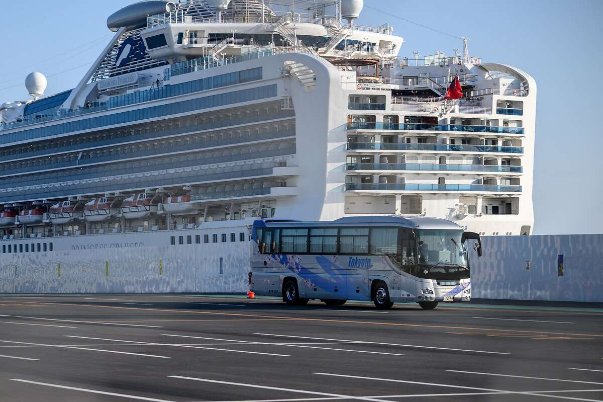 A bus drives through dockside past the Diamond Princess cruise ship, in quarantine due to fears of COVID-19 at Daikoku pier cruise terminal in Yokohama, Japan, on Feb, 21, 2020. Hundreds of people have been allowed to leave the ship after testing negative for the disease and many have returned to their home countries to face further quarantine.