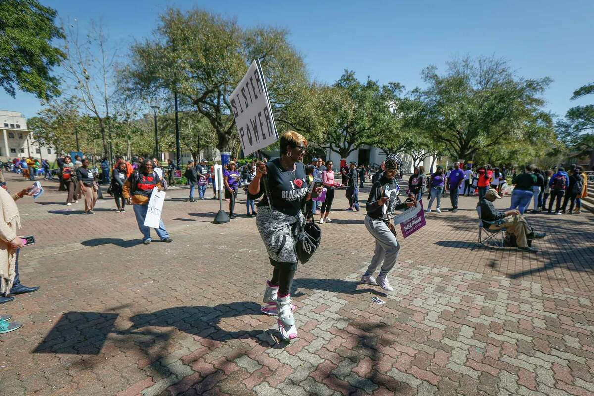 Gina Kay hold a sign and dances during a break of speakers during the Third Annual March for Black Women at TSU Saturday, Feb. 22, 2020, in Houston.